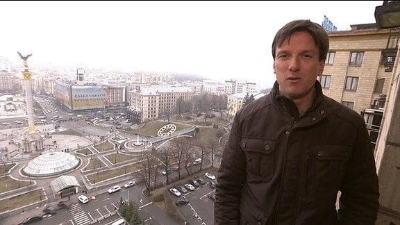 Ein Mann steht auf einem Balkon über dem Maydan in Kiew