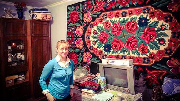 Eine Frau steht in ihrer Stube, im Hintergrund hängt ein Wandteppich.