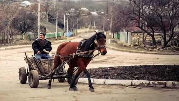 Mann fährt mit einem Pferdegespann auf einer Straße in einem Dorf.