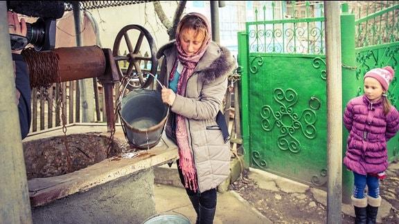 Frau an einem Brunnen in Cruglic