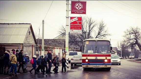 Schulkinder werden von einem Bus abgeholt.