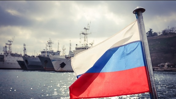 Russische Flagge vor Kriegsschiffen.