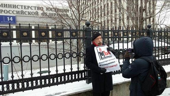 Demonstrant hält ein Plakat und wird fotografiert