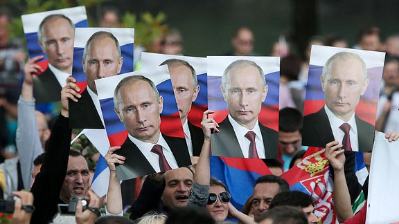 Menschen halten Putinplakate in den hochgereckten Händen.