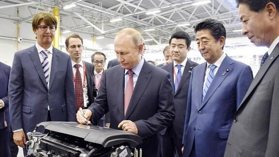 Der japanischer Premierminister Shinzo Abe (2. von R) und den russischen Präsidenten Wladimir Putin (C) besuchen eine Fabrik.