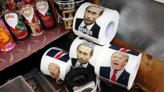 Klopapierrollen mit den Gesichtern von Putin und Trump auf einem Kiewer Markt.