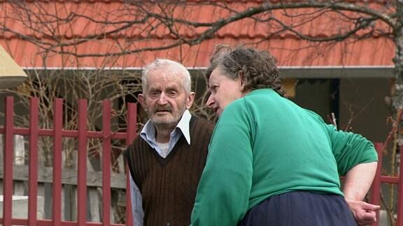 Zwei alte Bewohner von Putinovo stehen auf der Dorfstraße und unterhalten sich.