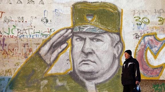 Ein Mann geht vor einem Wandgemälde des früheren Serben-Generals Ratko Mladic in einem Vorort von Belgrad entlang.