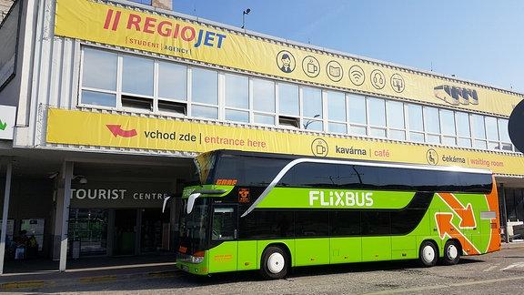 grüner FlixBus vor einem Prager Bus-Terminal mit RegioJet-Werbung