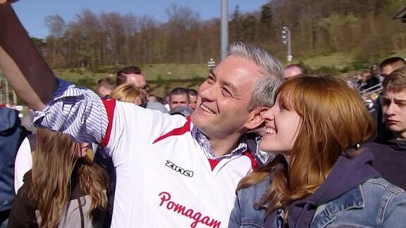 Grauhaariger Mann und junge rothaarige Frau machen Selfie auf einem Sportplatz.