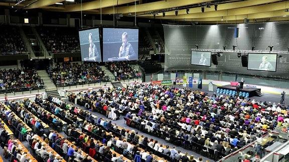 Blick auf eine Veranstaltung mit einem Podium und vielen Zuschauern