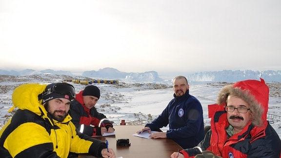 Männer sitzen bei eisiger Kälte im Freien