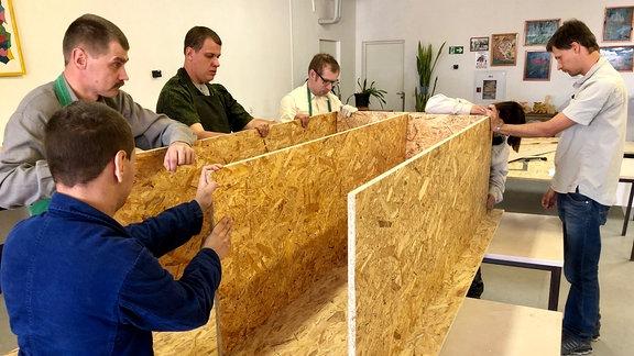 Männer bauen in Werkstatt Möbel