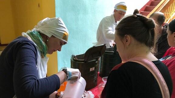 Helferin verteilt Lebensmittel