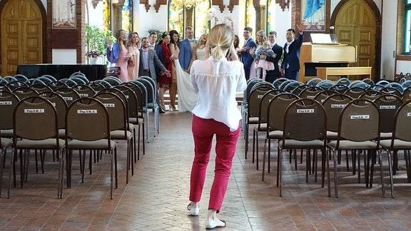 Frau in roter Hose und weißer Bluse fotografiert Hochzeitsgesellschaft in einer Kirche