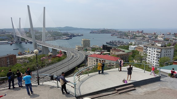 Menschen auf einer Aussichtsplattform. Dahinter eine Hafenstadt mit großer Autobahnbrücke.