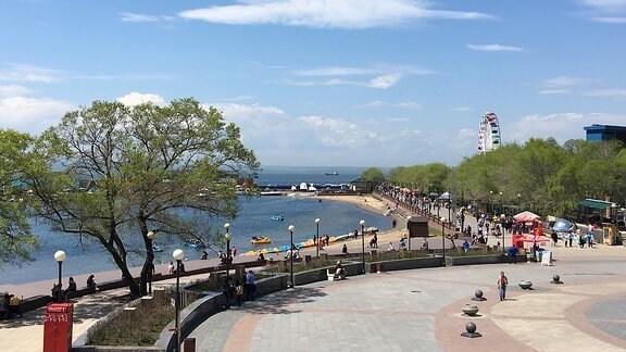 Strandpromenade mit buntem Riesenrad im Hintergrund