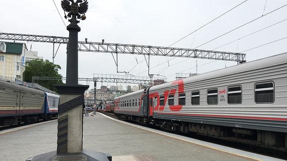 Silber-roter Passagierzug an einem Bahnsteig. Darauf eine Säule mit der Aufschrift 9288.