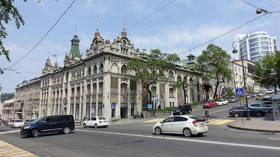 Prunkvoller, aber runtergekommener Kaufhausbau aus dem 19. Jahrhundert an einer befahrenen Kreuzung