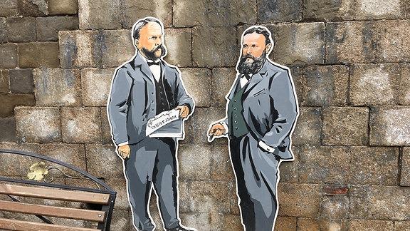 Auf Pappe angebrachtes Graffito von zwei Männern im Anzug an einer Mauer