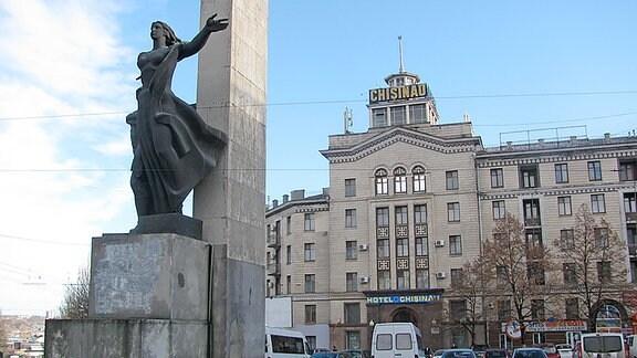 """Ein großes , mehrgeschossiges Wohnhaus im stalinistischen Baustil. Davor ein Denkmal für die Gefallenen des """"Großen Vaterländischen Krieges""""."""