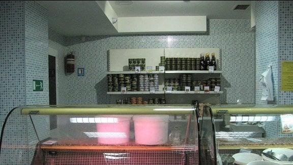 Blick in einen Laden mit gekachelten Wänden. Vorne eine Vitrine mit Fischen und Pasten.