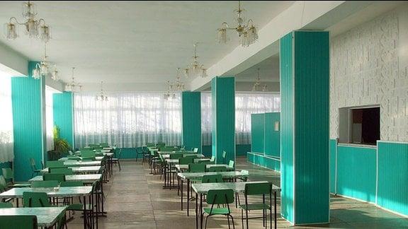 Ein schmuckloser Speisesaal. In dem flachen Raum mit türkisfarbenen, viereckigen Säulen, stehen nur Tische und Stühle.