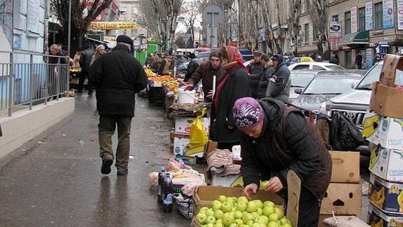Frauen mit Kopftüchern stehen an einer Straße und bieten Obst und Gemüse in Kartons an