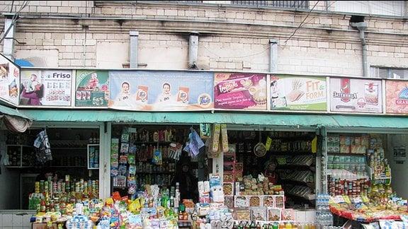 Blick von der Straße in ein sehr einfaches Ladengeschäft. Drinnen ist es sehr dunkel. Vor dem Geschäft, unter einem Vordach, stehen Plastikflaschen und Gläser. In Regalen liegen Lebensmittel.