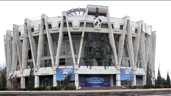 Ein imposantes rundes Gebäude aus Beton. Es ähnelt einem Stadion.