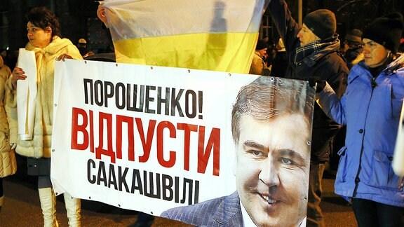 """Ukraine, Kiew: Demonstranten halten während einer Versammlung vor dem Marienpalast ein Banner mit dem Bild von Saakaschwili, dem früheren georgischen Präsidenten und der Aufschrift """"Poroschenko! Lass Saakaschwili gehen!"""" in den Händen."""