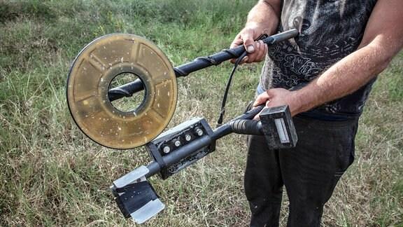 Ein Dorfbewohner zeigt seinen selbstgebauten Metalldetektor.