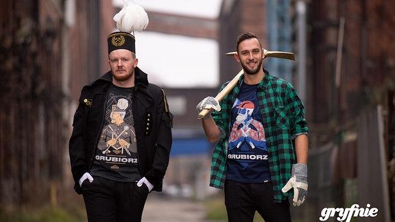 """Junge Männer präsentieren schlesische T-Shirts mit Bergbauer-Symbolen vom Hersteller """"Gryfnie"""""""