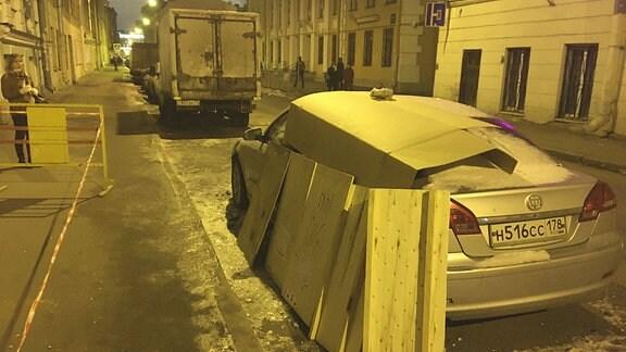 Ein Auto  ist mit Pappe und Holzplatten geschützt.