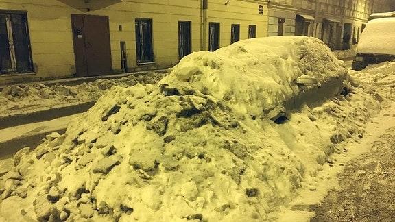 Ein unter Schneemassen begrabenes Auto steht am Straßenrand.