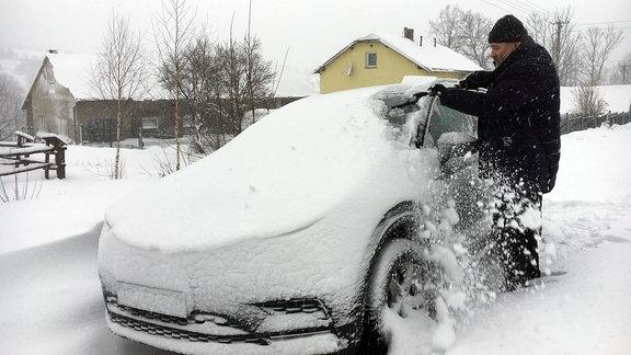 Mann schippt Schnee von PKW