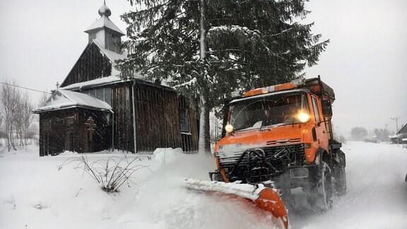 Schneepflug im Einsatz vor Holzkirche