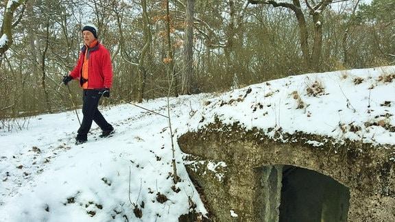 Ein Mann in roter Kleidung mit Nordic-Walking-Stöcken wandert im Schnee an einem Betonbunker vorbei.