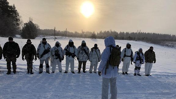 Mitglieder der Schützenunion stehen in einer Reihe und hören dem Instruktor zu