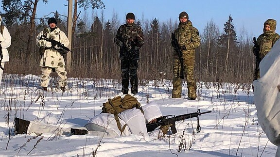 Ein Mann im weißen Anzug und mit einer Waffe in der Hand liegt auf dem schneebedeckten Boden
