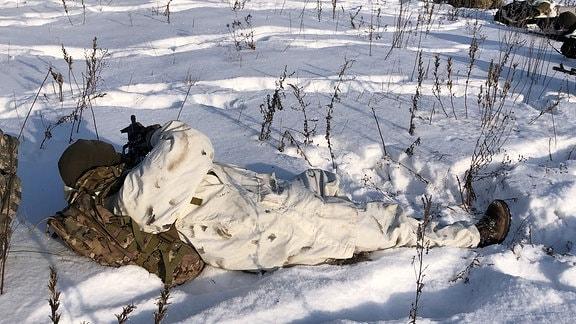 Ein Mann im weißen Schneeanzug mit einem Militärrucksack liegt auf dem Rücken im Schnee