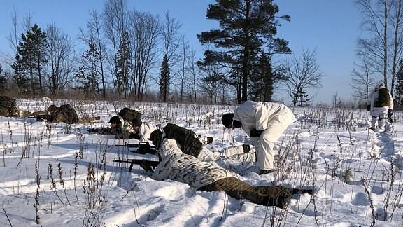 Die Hobby-Soldaten liegen mit Gewehr im Anschlag im Schnee