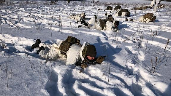 Ein Mann mit Schneeanzug und schwarzer Mütze robbt über ein Feld