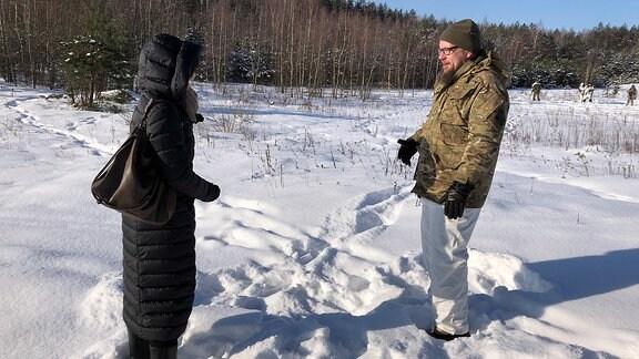 Die Journalistin Vytene Stasiatyte steht mit dem Leiter des Zugs bei der Schützenunion auf dem Feld und befragt ihn