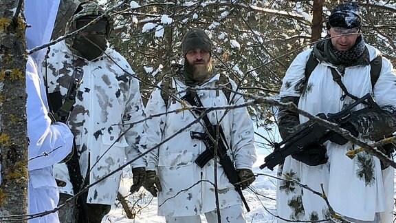 Männer mit Waffen und in Tarnkleidung stehen im Wald