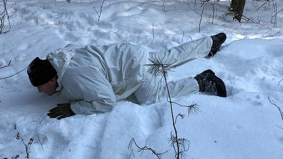Ein Mann im Schneeanzug und mit schwarzer Mütze sucht unter einem Baum Deckung