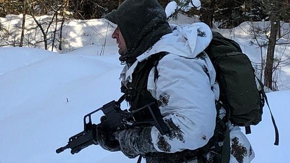 Ein Mann im Tarnanzug, Rucksack und einer Waffe in der Hand läuft durch den verschneiten Wald