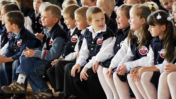 Lachende polnische Kinder in Schuluniform bei der Einschulungsfeier.