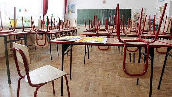 Ein leeres Klassenzimmer. Die Stühle sind auf die Bänke gestellt.