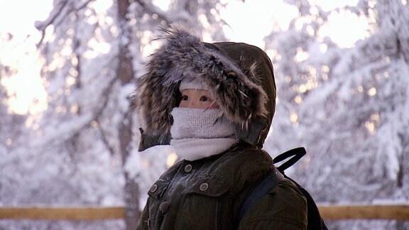 Ein winterlich eingepacktes Mädchen.